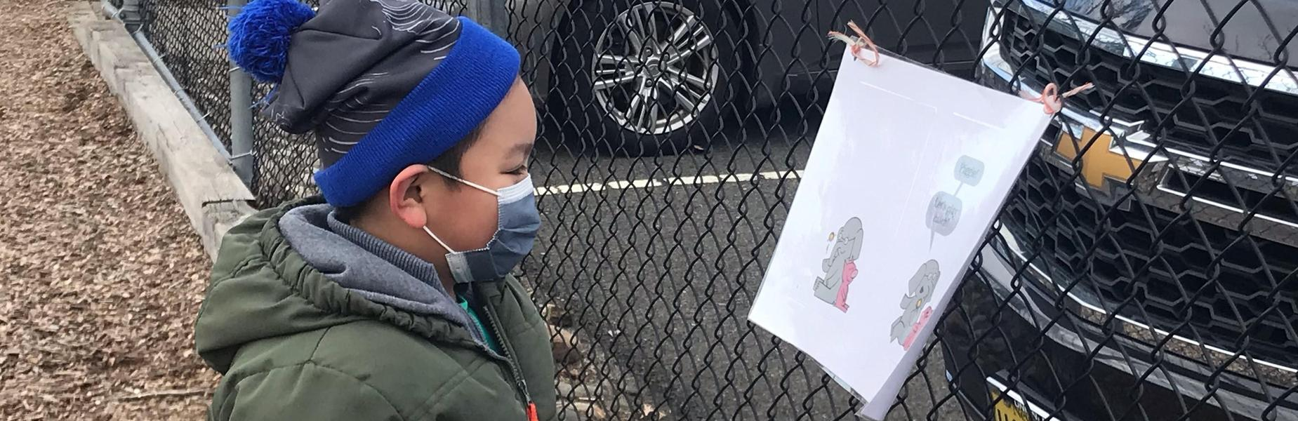 Photo of kindergartner reading a page on a playground Storywalk