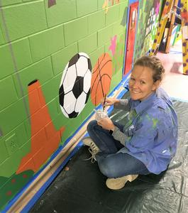 Parent volunteers at Jefferson Elementary School help to transform school hallways into a magical scene of the many events that take place each year.  A parent volunteer is pictured here painting the mural.