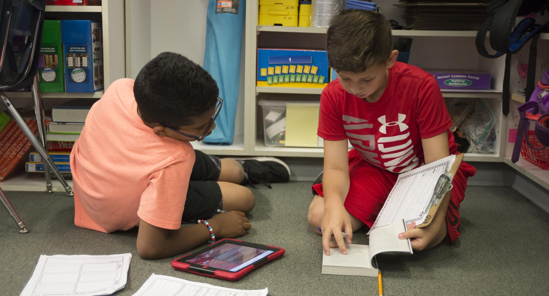 Two boys work on assignment on floor of classroom.
