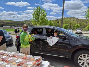 In honor of National Teacher Appreciation Week, a student from Sloan Elementary presents a flower to his 3rd Grade teacher, Mrs. Chris Hong (shown) at the Grab 'n Go distribution line.   Mrs. Hong along with Dr. Tawnia St. Amant, Linda Miller, Tim Skoog, Christine Nicely, Suzanne Robbins, Kylie Hadley, Michelle Ferace, and Danielle Hartman volunteered to hand out meals to students today.