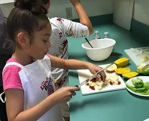 Young girl dressed in pink top and an apron chops apples.