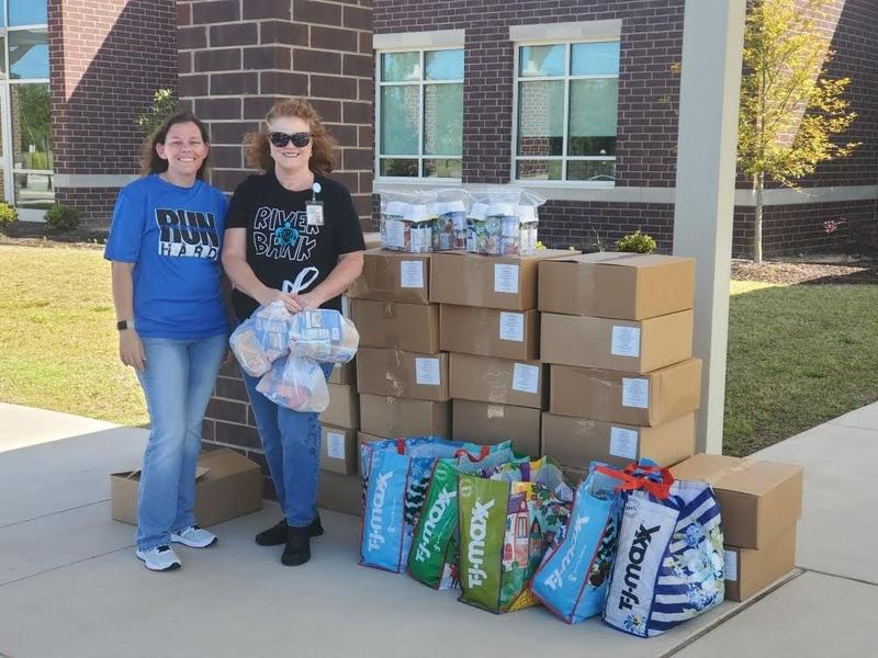 Riverbank Elementary nurse Ruth Neese, right, along with fellow Riverbank nurse Jessica Wahl, get ready to distribute snack packs recently at the drive-thru meal line at the school.
