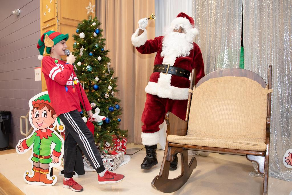 A student holds a microphone laughs as Santa rings a bell