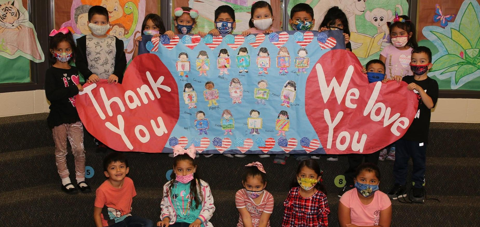 Students hold up thank you sign