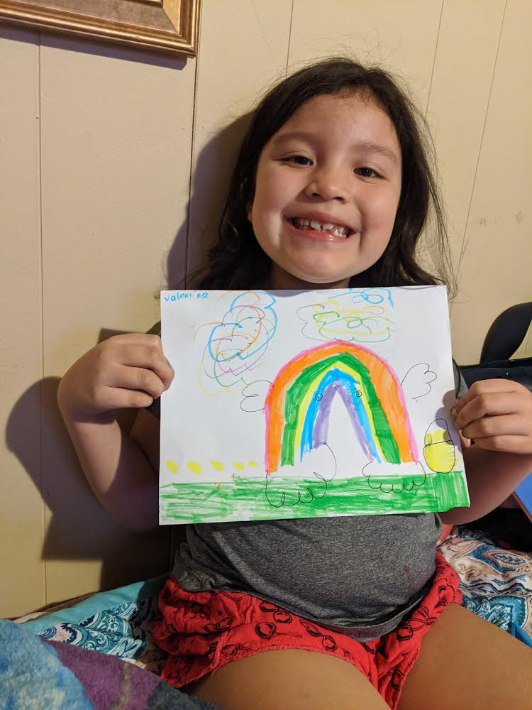 female student showing off her rainbow drawing