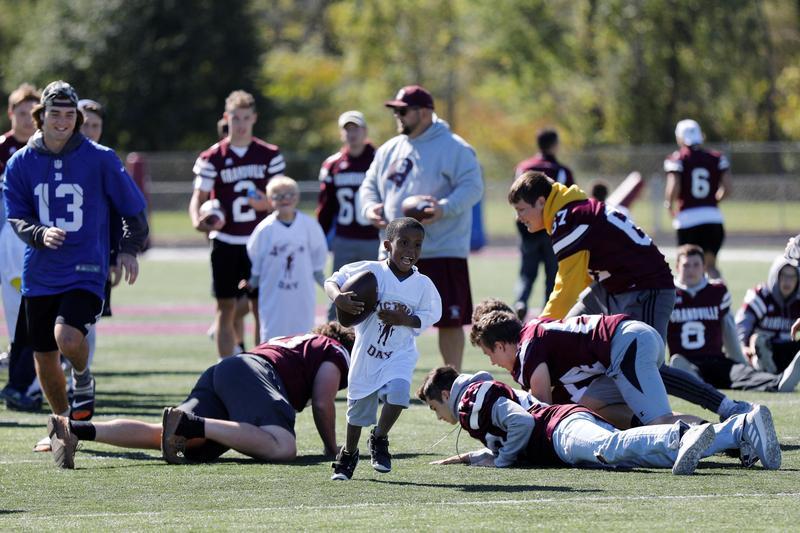 boy runs for touchdown while varsity team surrounds him