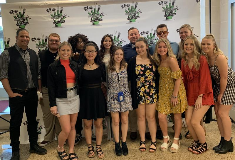13 boys and girls along with their teacher standing in front of the Greenfield Youth Film Festival backdrop. These students competed in the film fest.