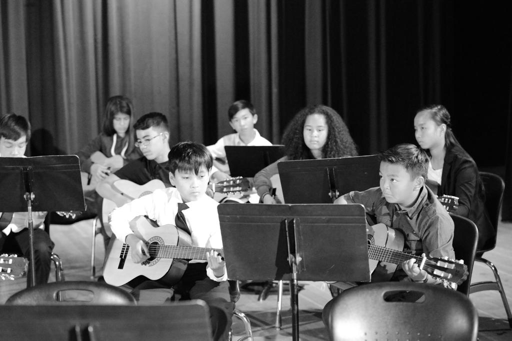 Black and white photo of students playing guitar.