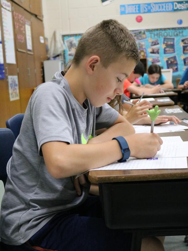 Washington School 5th grader Jake Stinton writes a letter to himself which will be mailed to him by his teacher, Matthew Cognetti, when Stinton graduates from high school.