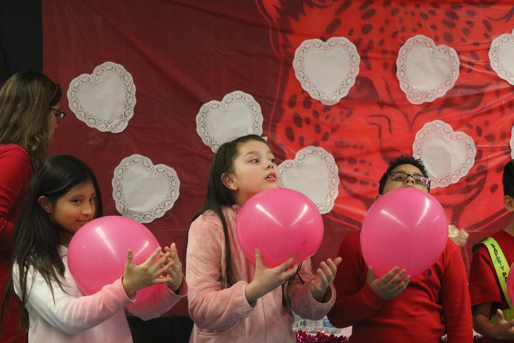 three kids holding pink balloons to their chins