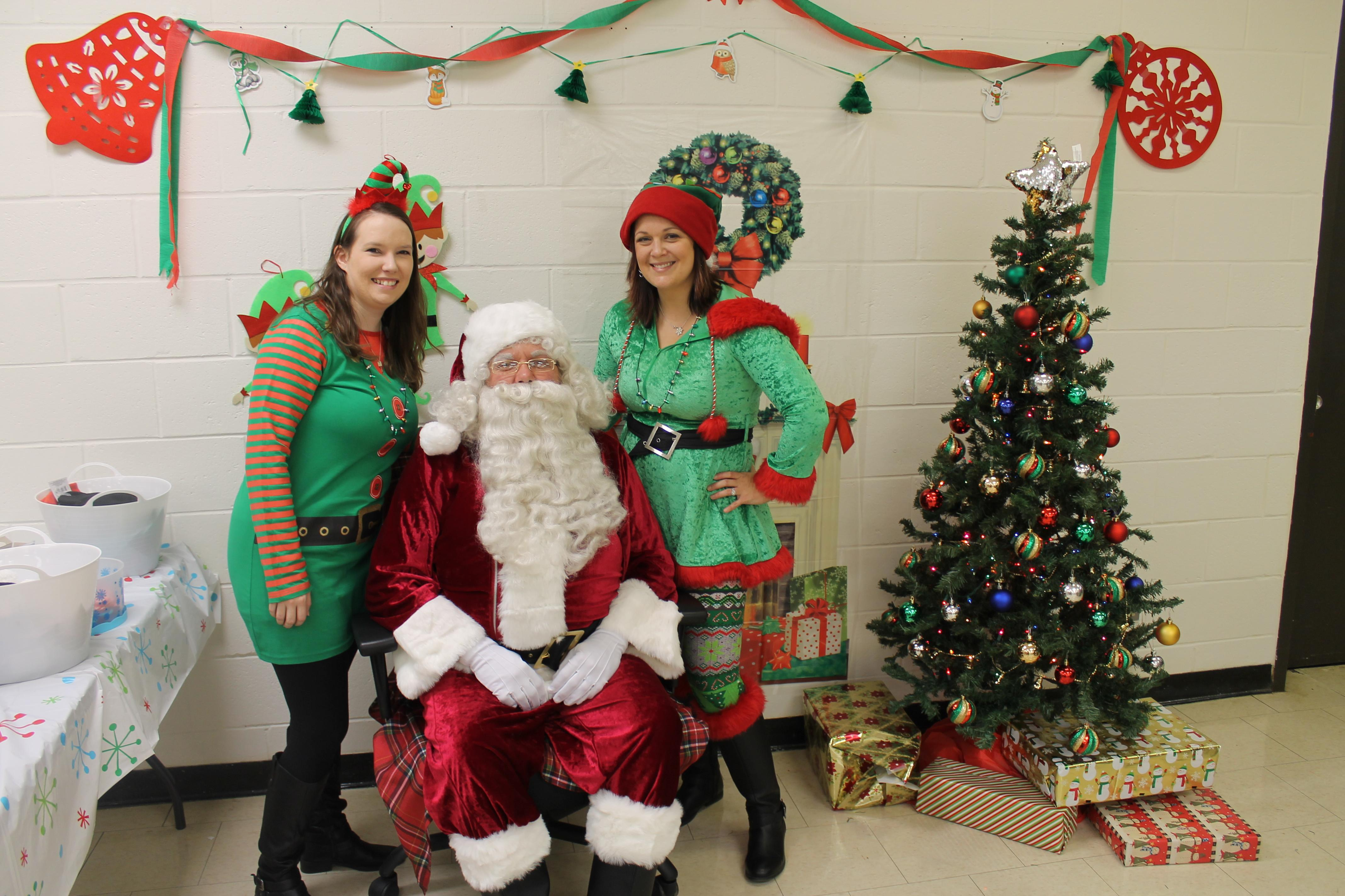 two women dressed as elves with santa