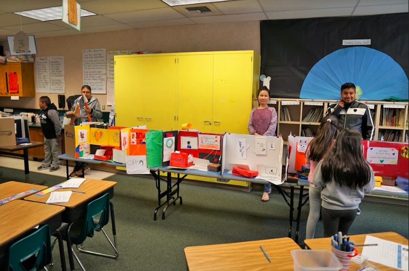 snapshot of projects on display and parents and students roaming the classroom