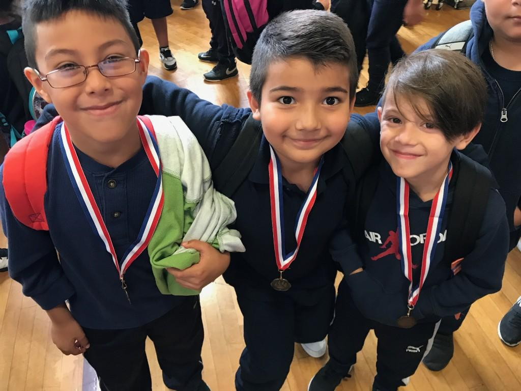 3 students smiling with their medals