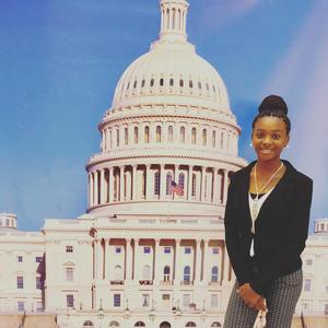 a photo of Baker Middle Student Destiny Jones in front of a backdrop of the US Congress Building