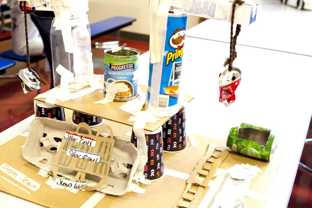 A creative project featuring a Pringles container, cups and containers