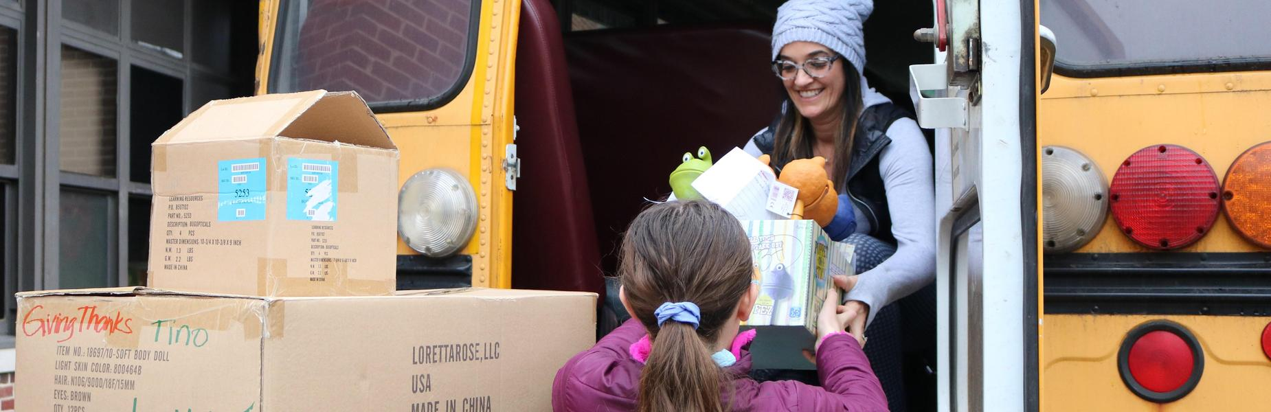Photo of Franklin student handing box of toys to staffer on bus.