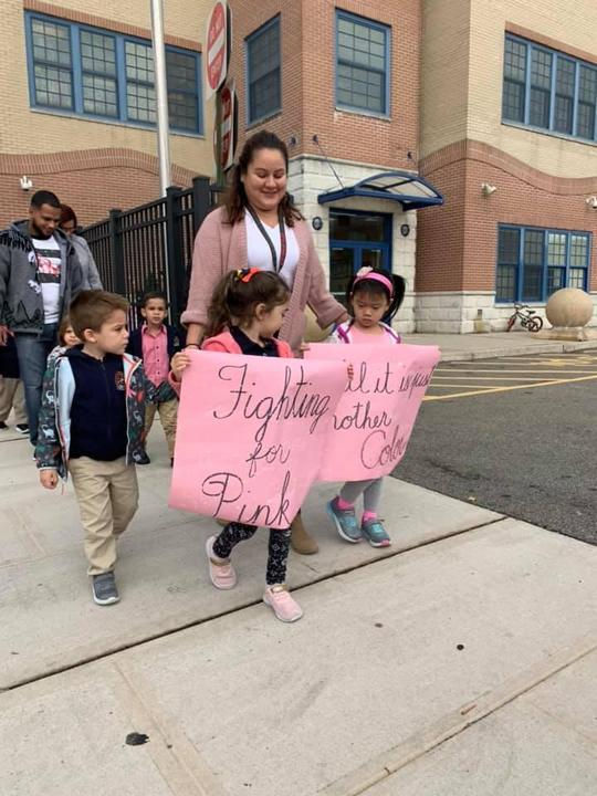 three kids heading other students while holding a banner that say fighting for pink