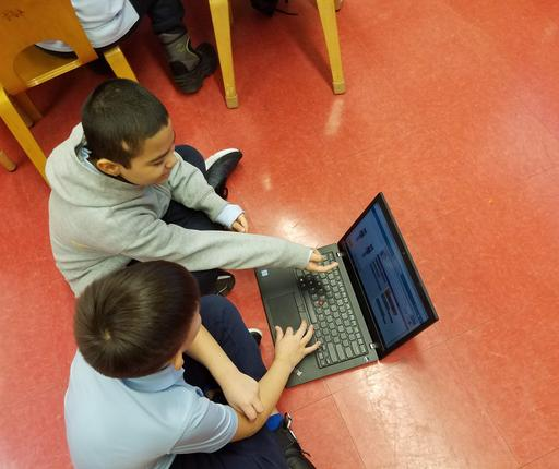 Two 2nd grade students Coding, sitting on floor with laptop- CS4ALL Day 2019