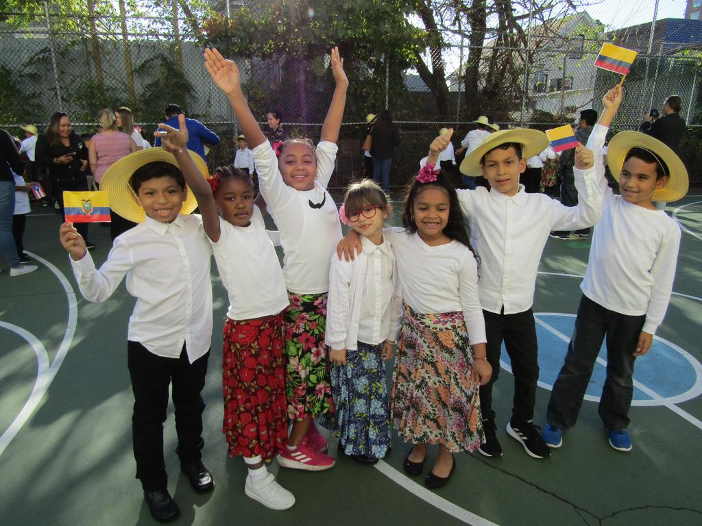 a group of boys and girls dressed in their performance costume with hands up in the air