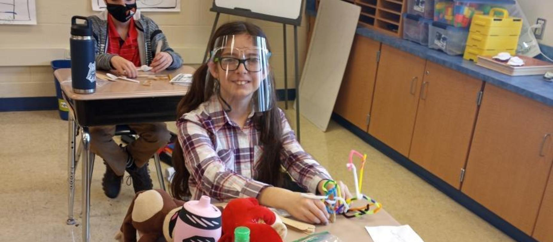 girl wearing a face shield working on a project