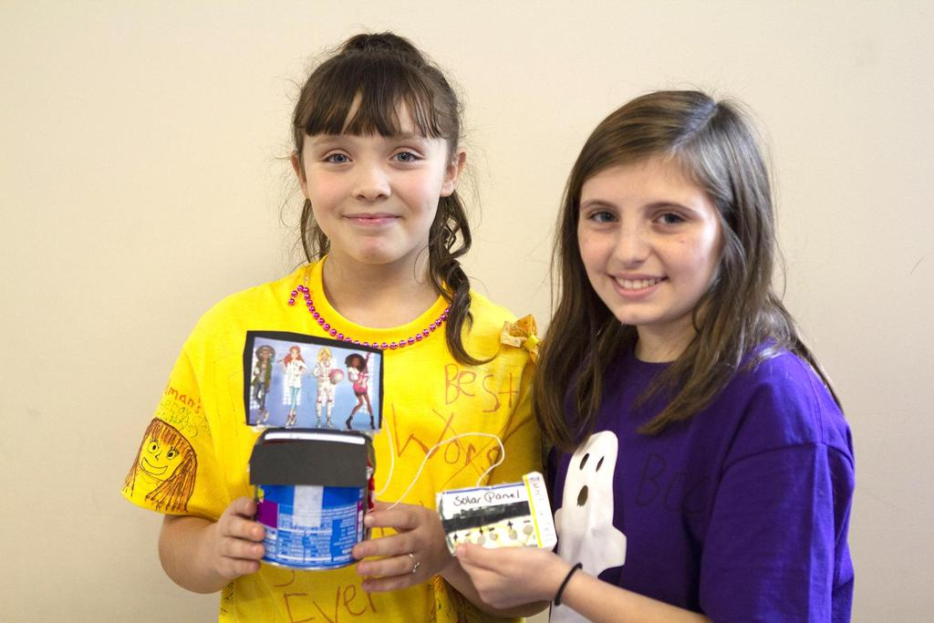 Two students hold up their STEM projects for the camera