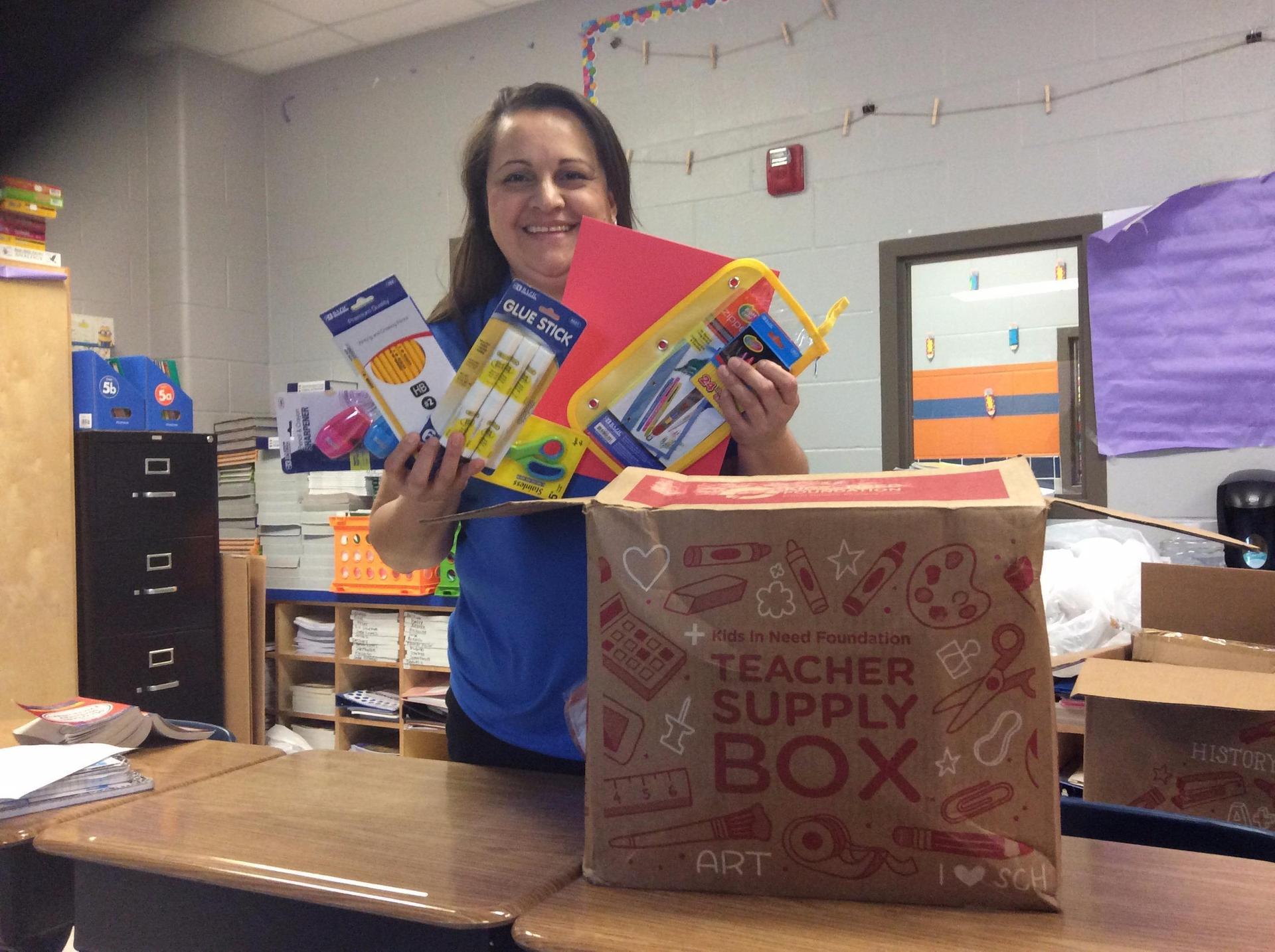 Image of Mrs. Guzman receiving school supplies for Gorena Elementary