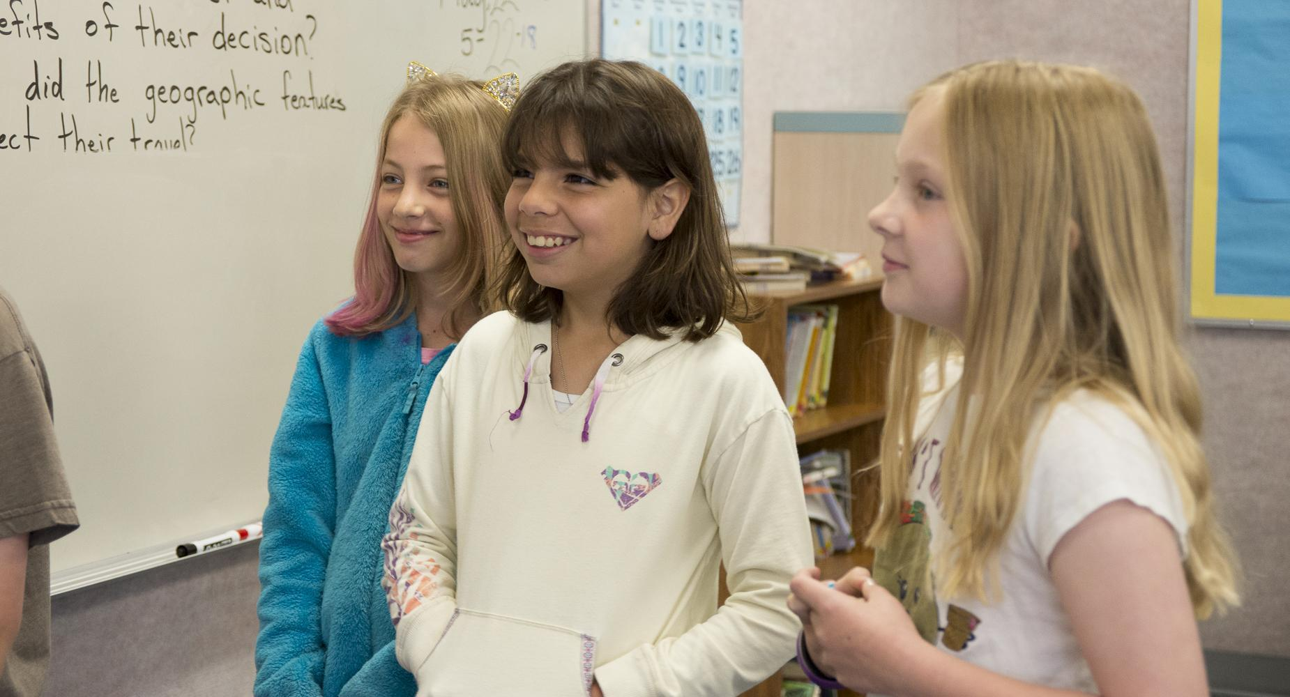 Three girls stand together in the classroom