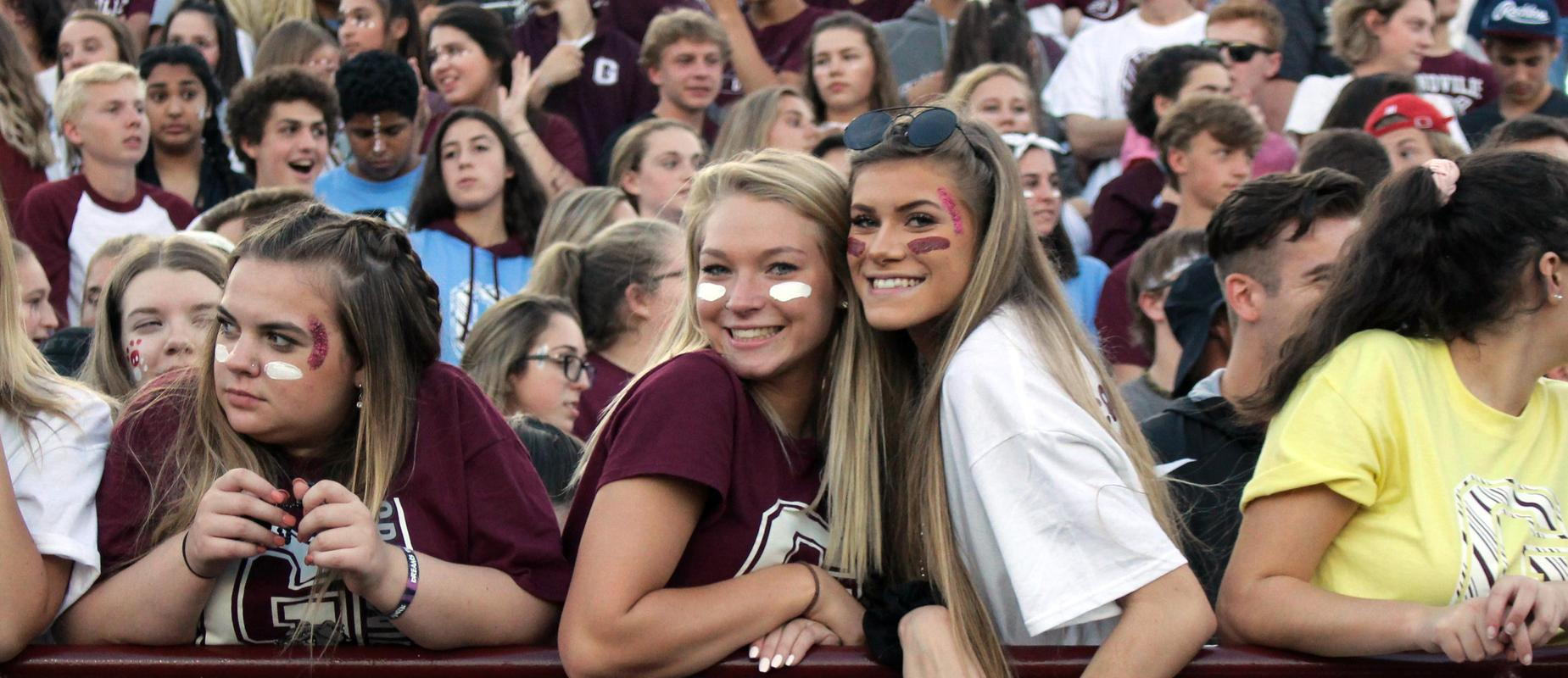 crowd wears school colors at homecoming football game