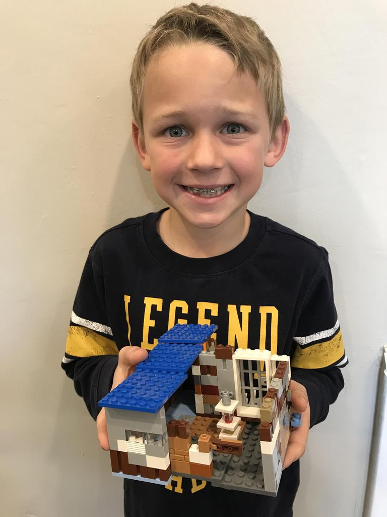 picture of boy holding lego house he built