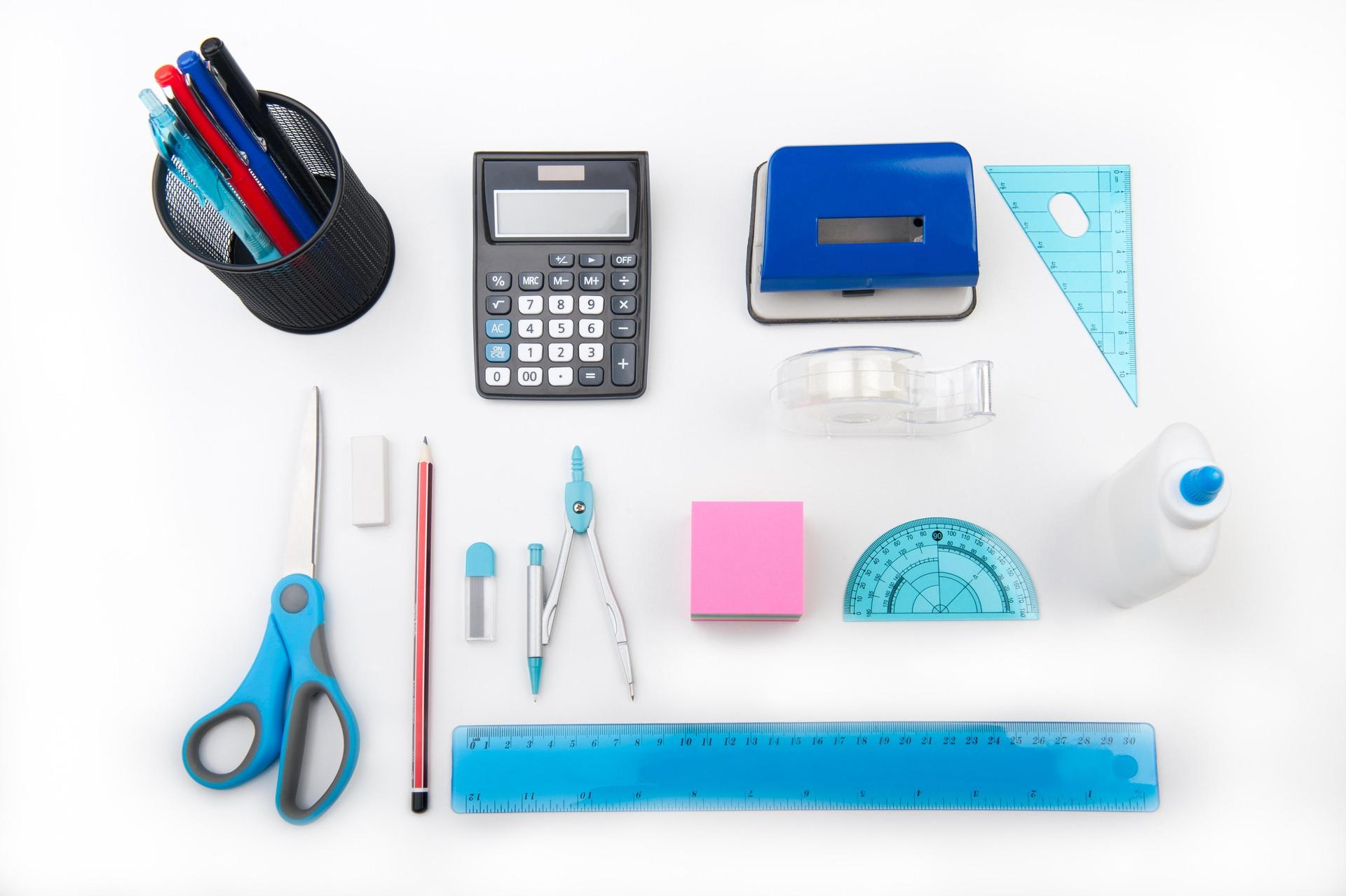 Picture of school supplies including a pencil cup with pencils in it, calculator, scissors, protractor, ruler, eraser