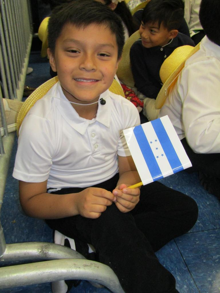 close up of a boy sitting on the floor holding a flag in his hand