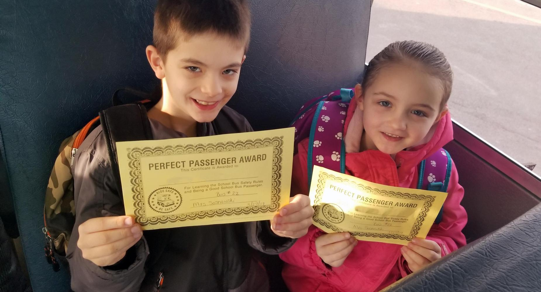 students on bus holding award