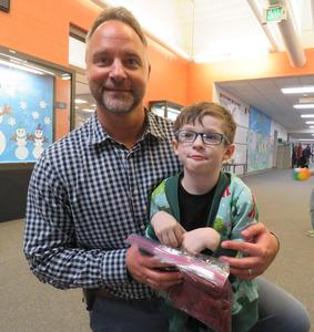 Zac gives a special pair of mittens to McFall Principal Jon Washburn.