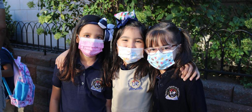 3 girls wearing masks outside