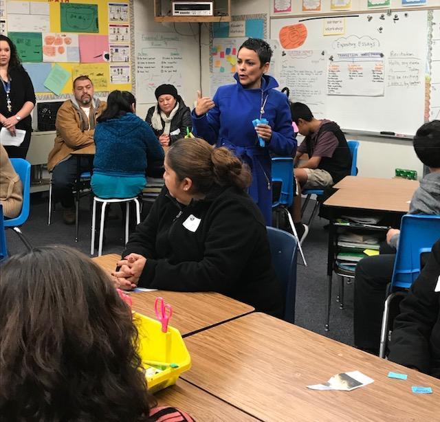 Teacher talking to parents in classroom