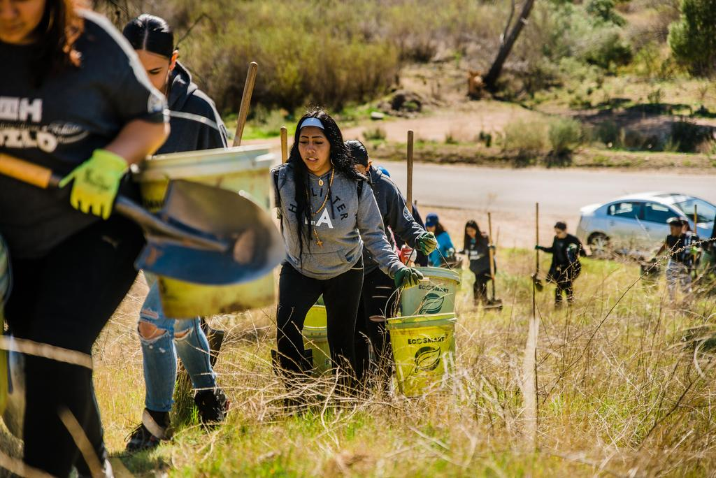 Lennox students carry tree planting supplies up a hill