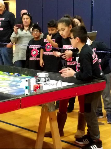 Two students look closely at their robot on a playing surface