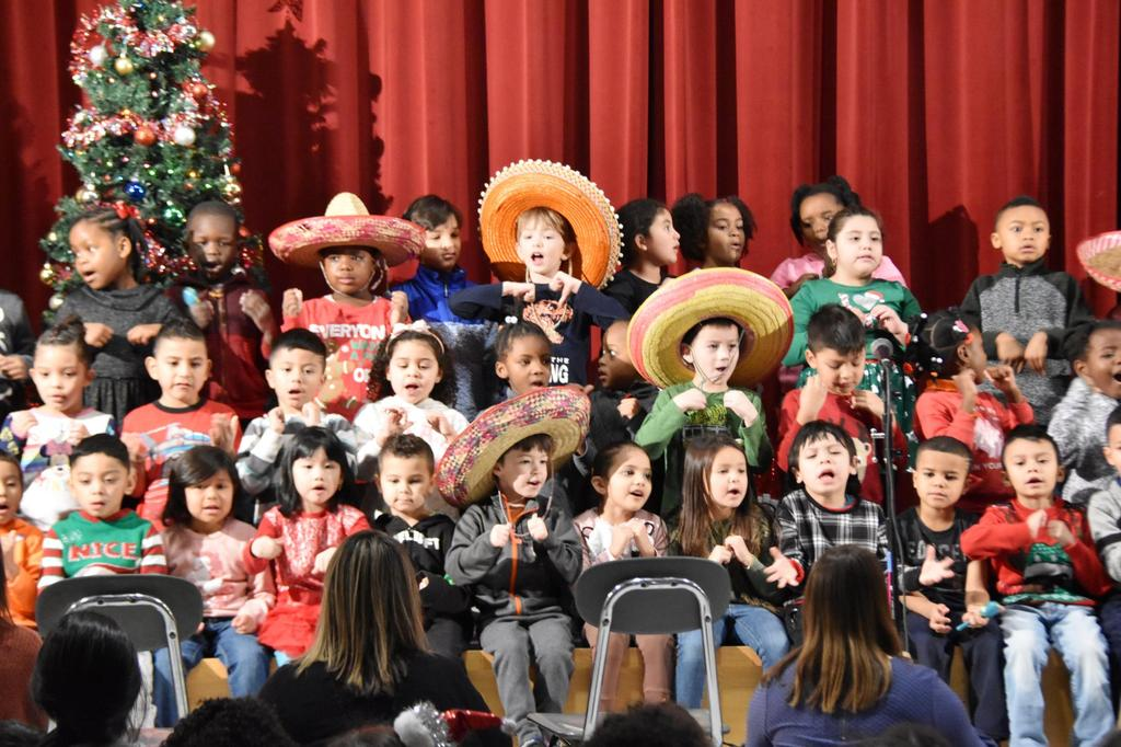 A section of a stage filled with young students, many of whom are wearing sombrero hats