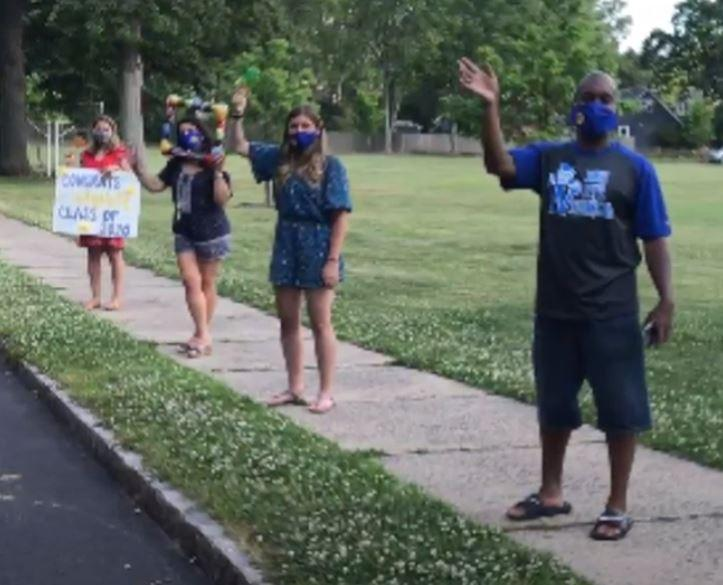Photo of Jefferson teachers lined up and waving during Grade 5 Clap Out Car Parade.