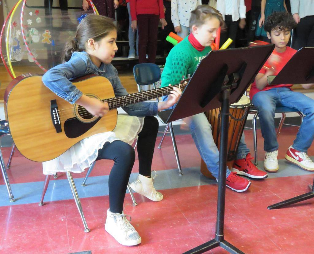 A girl plays the guitar next to two boys playing percussion instruments