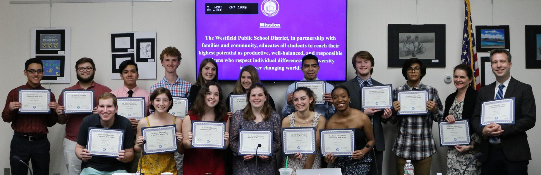 Photo of Westfield High School Chorus students and their instructors holding certificates of recognition at May 21 Board of Education meeting.