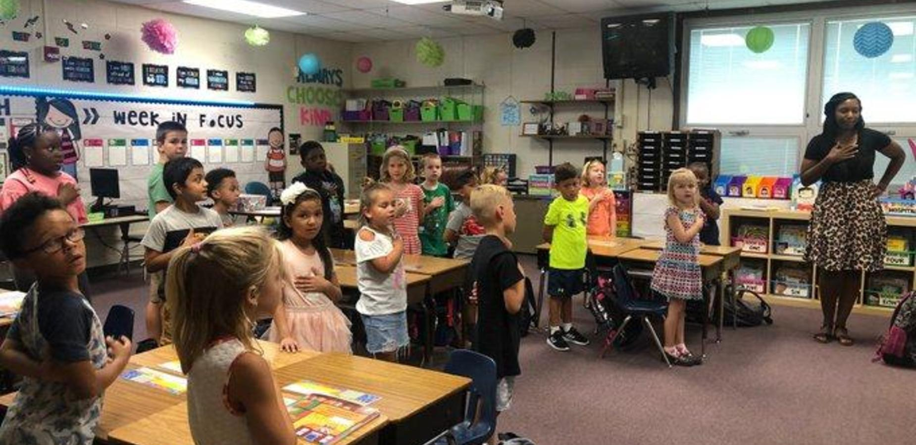 This is an image of a classroom with the teacher and her students reciting the Pledge of Allegiance to the flag in their classroom. The students all have their hands over their hearts.