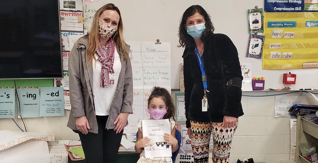 Principal Takaki, Mrs. Bergin and Daniella. Daniella is holding the story she wrote and read to the class