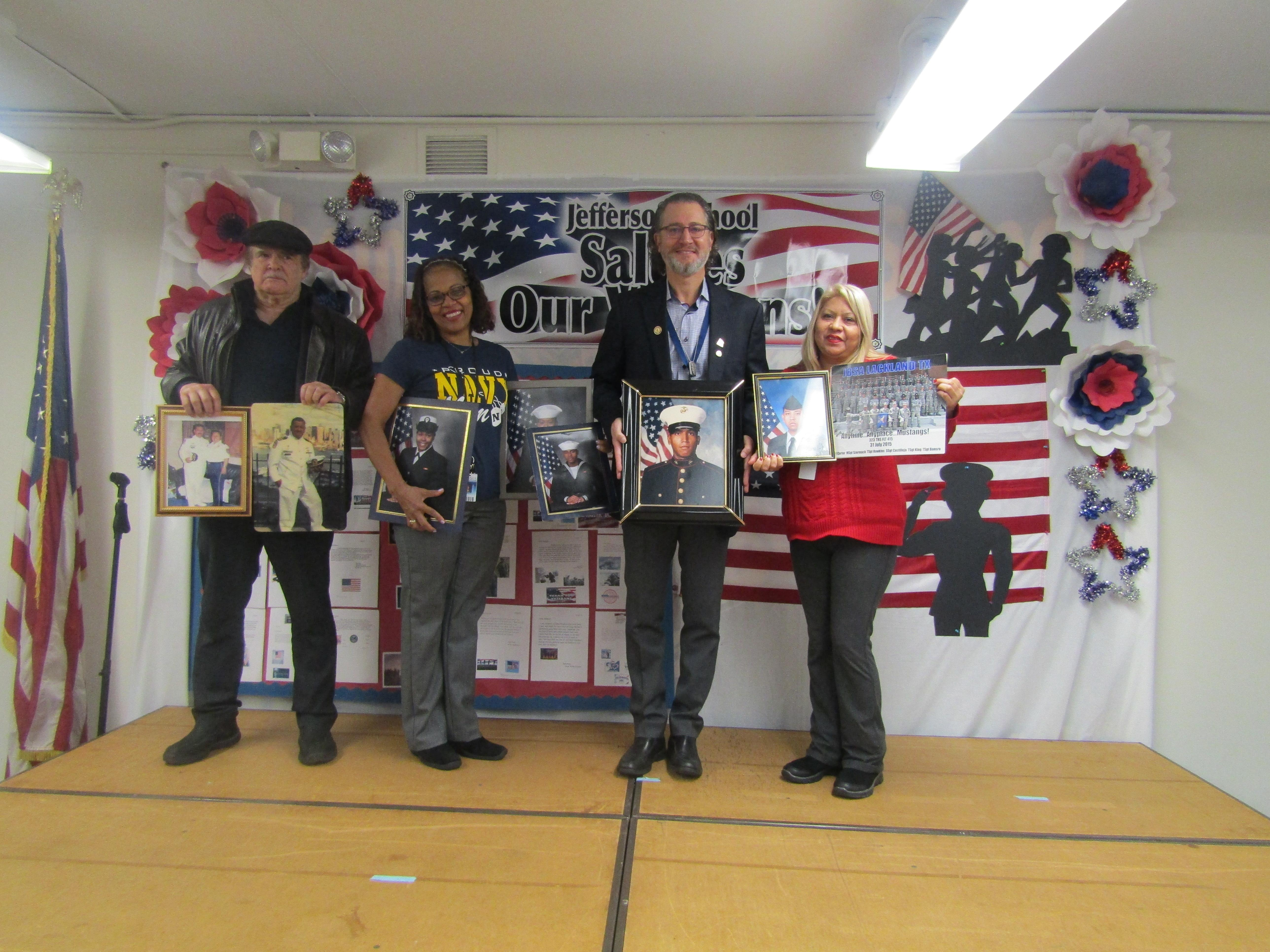 three families proudly standing with photos of their family members who are in service