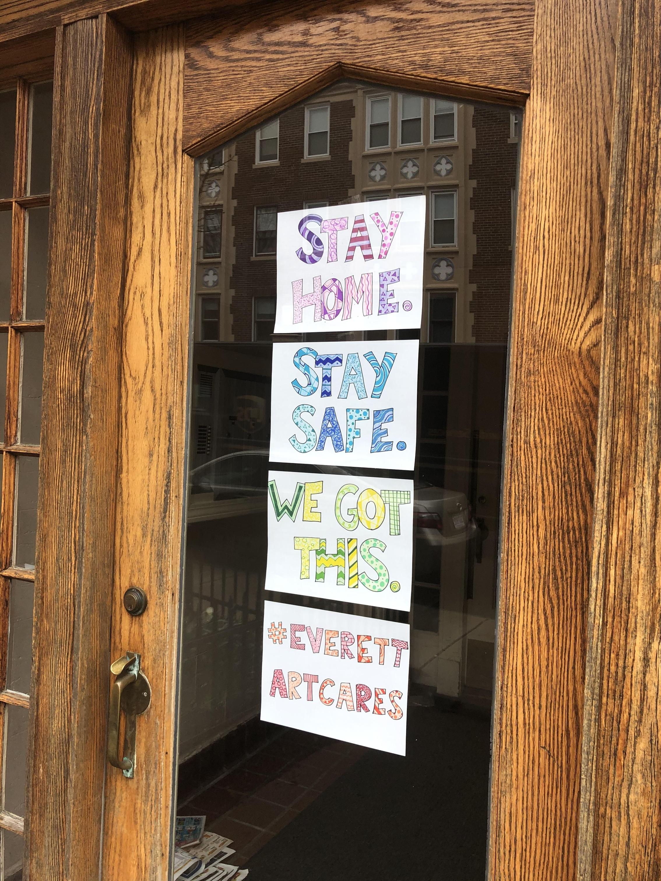 A door decorated with three signs that read 'Stay home,' 'stay safe,' and 'we got this'