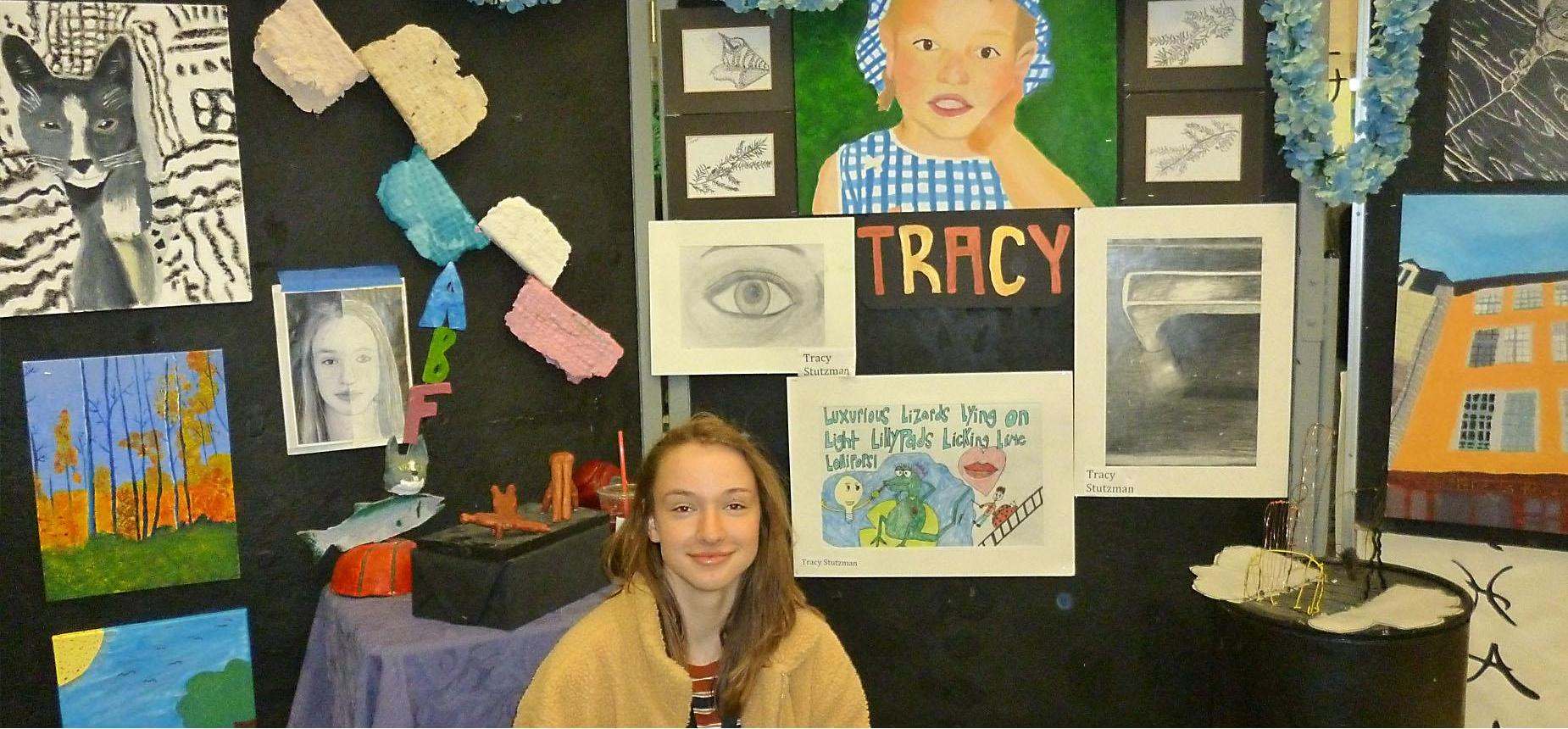 Student posing in front of her art display at the Senior Art Exhibition