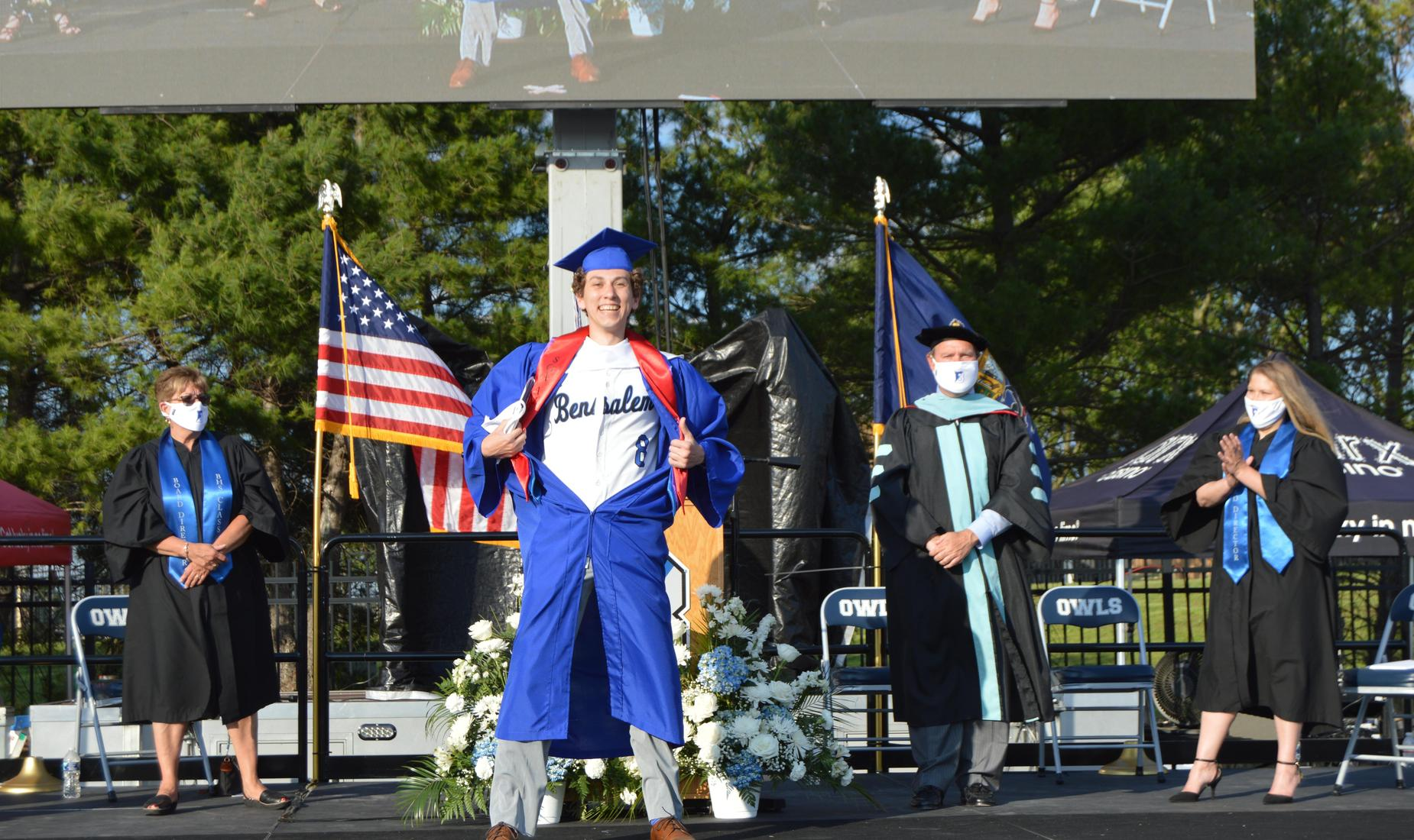 BHS senior dressed by blue cap and gown opens gown to show his baseball jersey, Bensalem #8