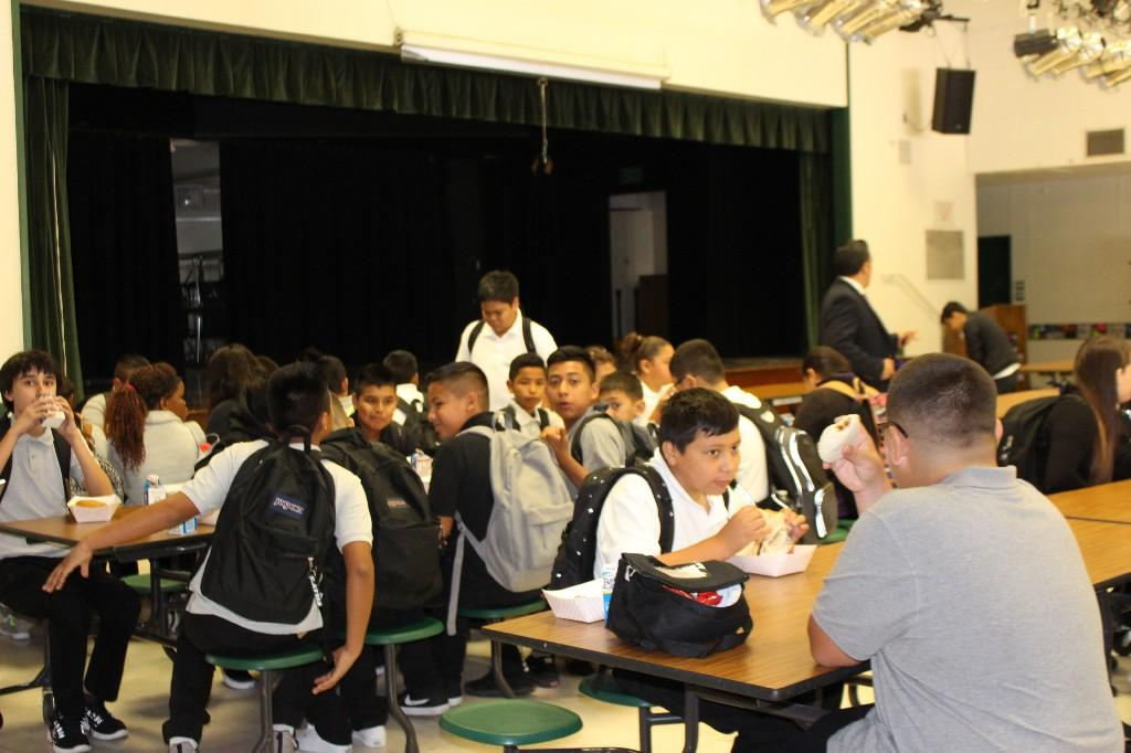 many students sit in a cafeteria in the Bridges Academy cafeteria