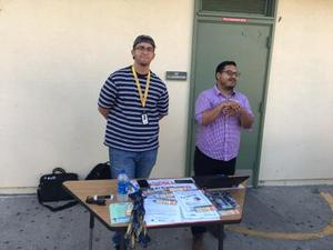 two people in the Bridges Academy courtyard standing behind a table with literature displayed on the table