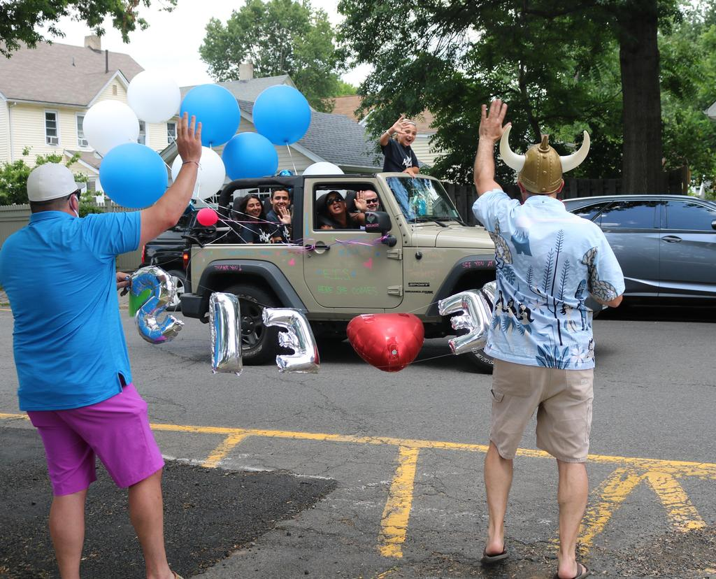 Photo of McKinley 5th grade teachers enthusiastically waving to 5th grader passing by during Grade 5 Clap Out Car Parade